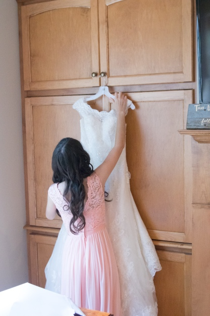 Christ Baptist Church Wedding, Raleigh NC: A bridesmaid gets the brides gown out of the cover and hangs it from a knob.